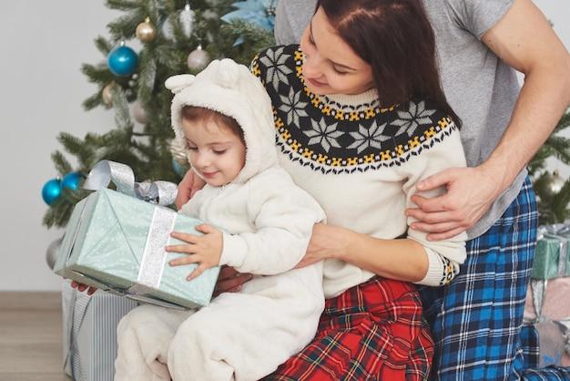 Famiglia felice a natale nei regali di apertura di mattina insieme vicino all'albero di abete. il concetto di felicità e benessere familiare