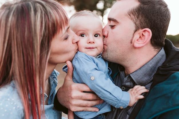 Famiglia felice all'aperto al tramonto, padre, madre e figlio al parco. concetto di famiglia