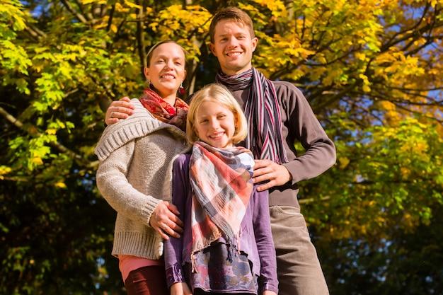 Famiglia felice all'aperto che si siede sull'erba in autunno