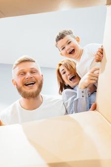 Famiglia felice appena trasferita nella nuova casa e guardando la scatola