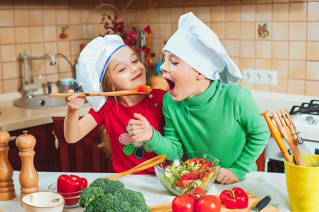 Famiglia felice bambini divertenti stanno preparando un'insalata di verdure fresche in cucina