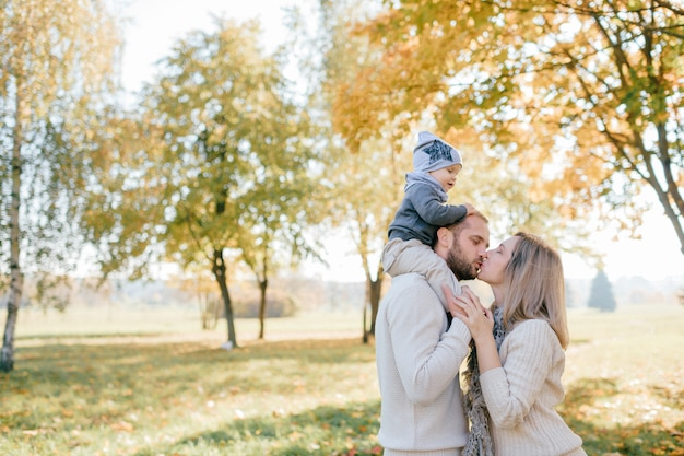 Famiglia felice che bacia con il loro bambino sulle spalle nel parco di autunno.