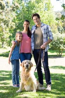 Famiglia felice che cammina con il loro cane nel parco
