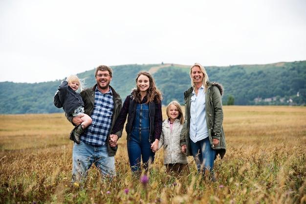 Famiglia felice che cammina in un campo