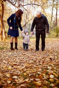 Famiglia felice che cammina nel parco d'autunno