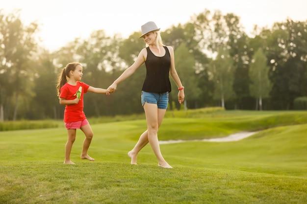 Famiglia felice che cammina sui campi di erba
