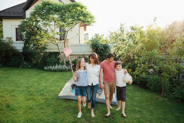 Famiglia felice che cammina sull'erba davanti alla tenda all'aperto