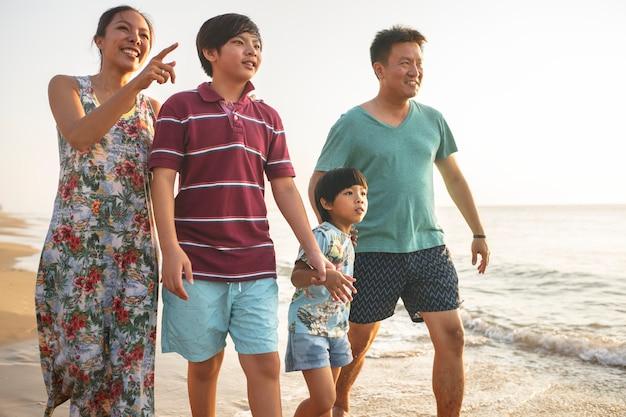 Famiglia felice che cammina sulla spiaggia