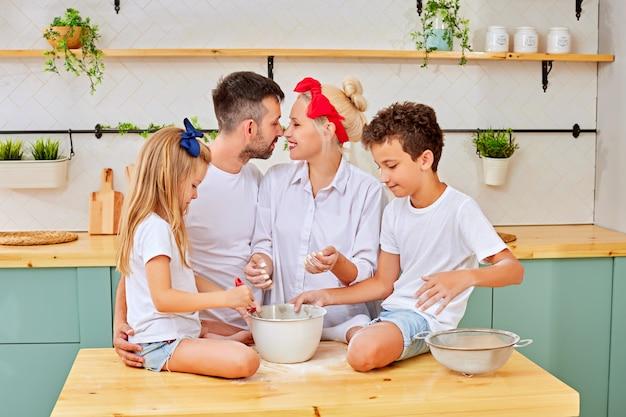 Famiglia felice che cucina insieme nella cucina alla moda
