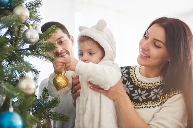 Famiglia felice che decora insieme l'albero di natale. padre, madre e figlia. bel bimbo