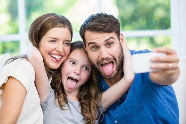Famiglia felice che fa i fronti mentre si fa clic su selfie