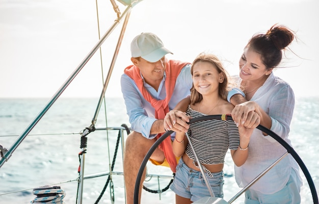 Famiglia felice che fa viaggio di lusso in barca a vela - padre, madre e figlia si divertono a viaggiare nel mar dei caraibi