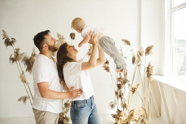 Famiglia felice che gioca a casa con il loro bambino su uno sfondo bianco con canne