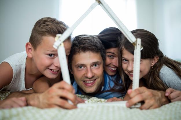Famiglia felice che gioca con la casa di modello in camera da letto