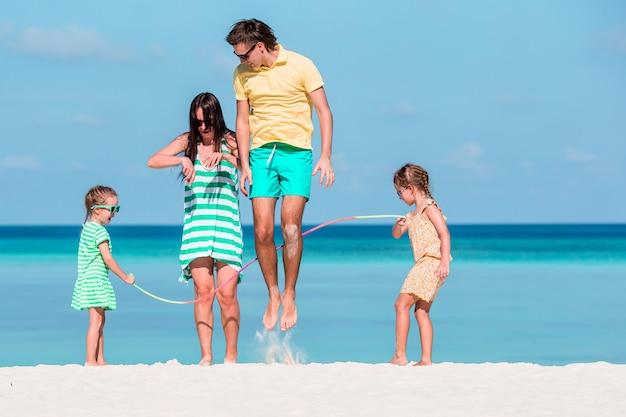 Famiglia felice che gioca insieme sulla spiaggia bianca