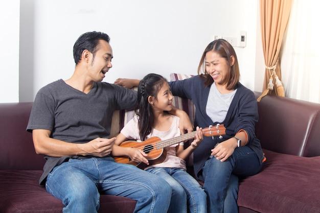 Famiglia felice che insegna alla figlia a suonare l'ukulele