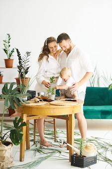 Famiglia felice che lavora a casa. trapiantare le piante con il loro bambino