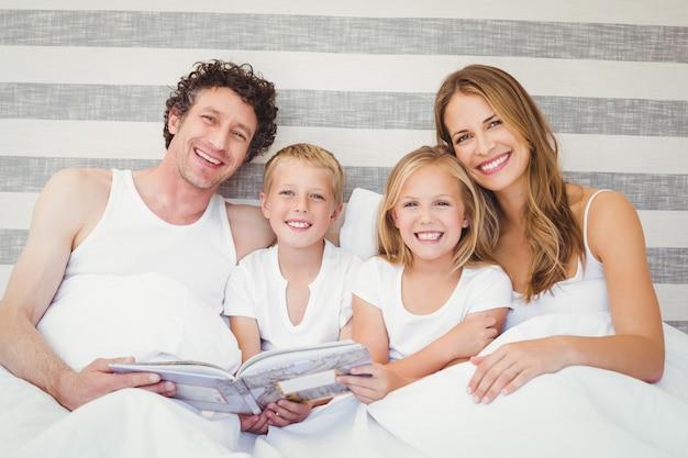 Famiglia felice che legge un libro sul letto
