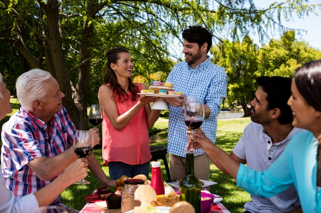Famiglia felice che mangia i bigné e vino rosso in parco