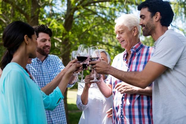 Famiglia felice che mangia vino rosso in parco