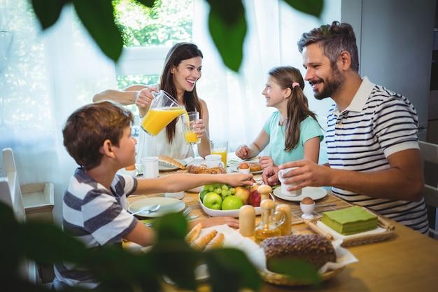 Famiglia felice che parla l'un l'altro mentre facendo colazione insieme