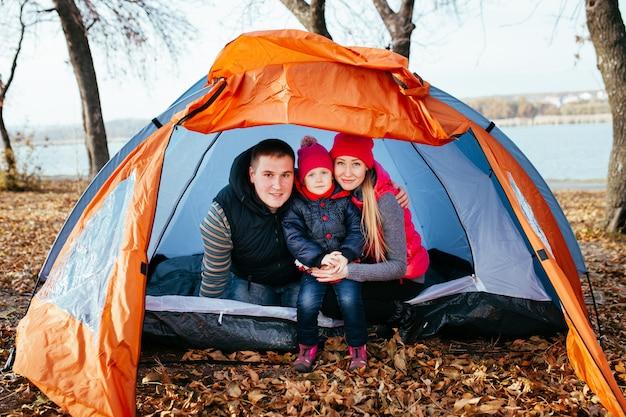 Famiglia felice che posa seduta in una tenda