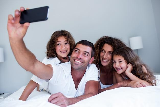 Famiglia felice che prende un selfie sul letto