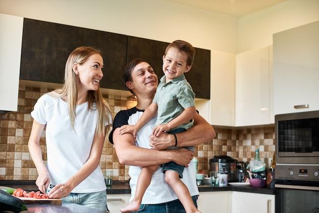 Famiglia felice che prepara insieme le verdure a casa nella cucina.