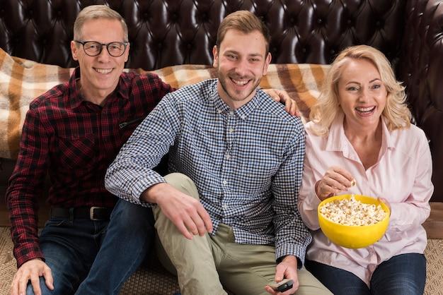 Famiglia felice che propone con la ciotola di popcorn