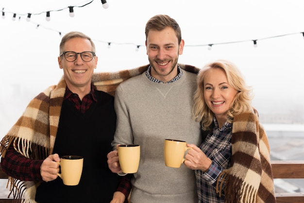 Famiglia felice che propone con le tazze