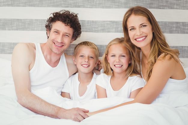 Famiglia felice che si distende sul letto