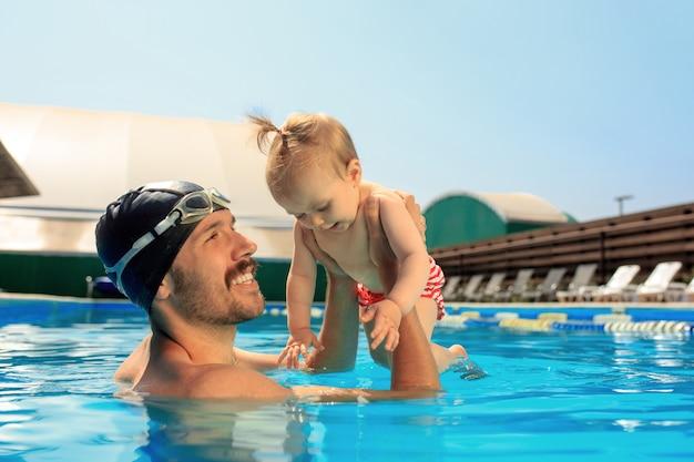Famiglia felice che si diverte a bordo piscina