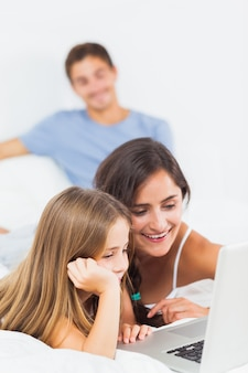 Famiglia felice che si siede con un computer portatile