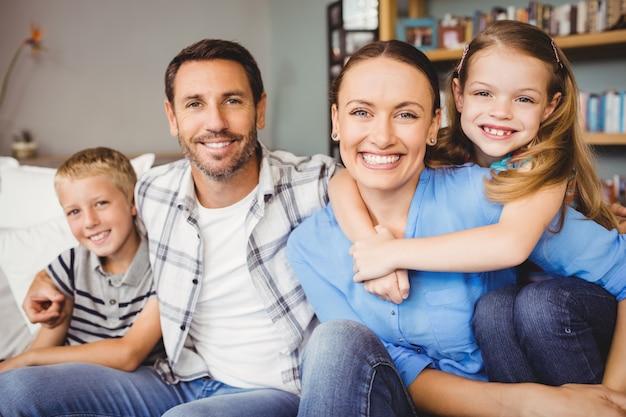 Famiglia felice che si siede sul sofà contro lo scaffale