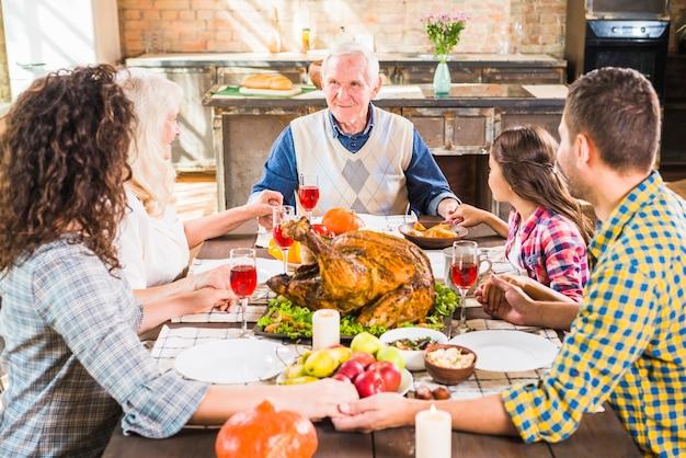 Famiglia felice che si tiene per mano al tavolo con il cibo