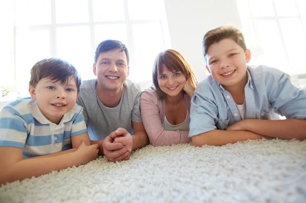 Famiglia felice che si trova giù su un tappeto bianco