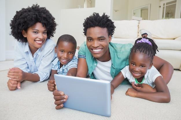 Famiglia felice che si trova sul pavimento facendo uso della compressa