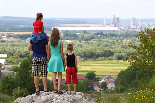 Famiglia felice che sta stante su una roccia in montagne. concetto di famiglia amichevole.