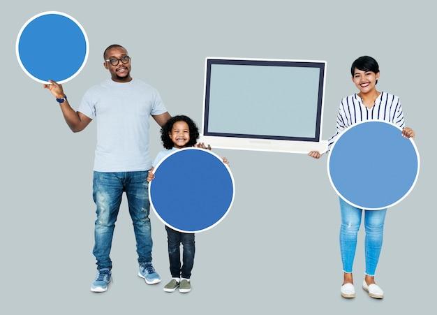 Famiglia felice che tiene tavole rotonde e uno schermo