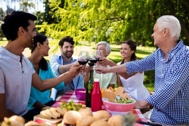 Famiglia felice che tosta un bicchiere di vino