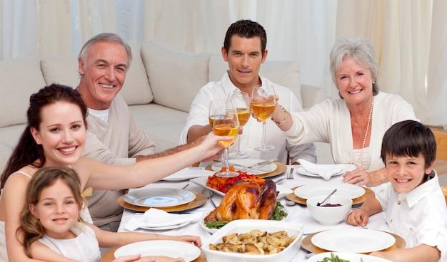 Famiglia felice che tusting con vino in una cena