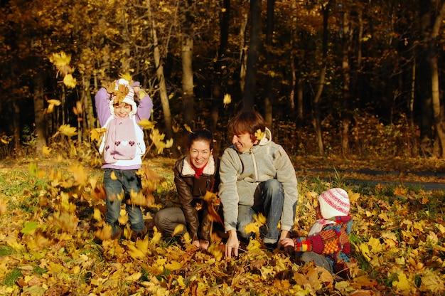 Famiglia felice con due bambini che gettano le foglie nel parco di autunno