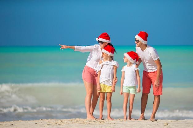 Famiglia felice con due bambini in santa hat in vacanza estiva