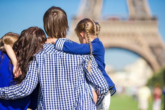 Famiglia felice con due bambini vicino alla torre eiffel in vacanza a parigi