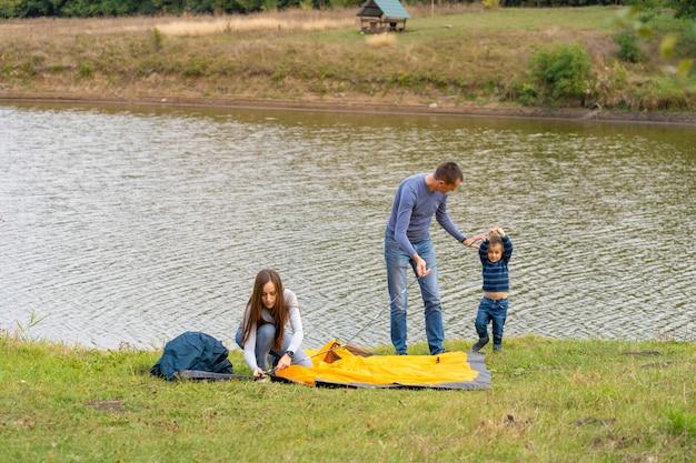 Famiglia felice con figlio piccolo installato tenda da campeggio, infanzia felice, viaggio in campeggio con i genitori, un bambino aiuta a installare una tenda