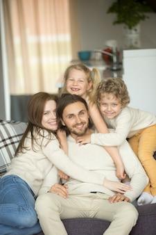 Famiglia felice con i bambini sul sofà che guarda l'obbiettivo, ritratto