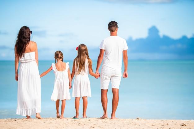 Famiglia felice con i bambini sulla spiaggia insieme