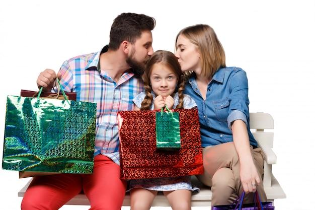 Famiglia felice con la seduta di borse per la spesa