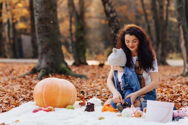 Famiglia felice con piccolo bambino sveglio nel parco sulla foglia gialla con grande zucca in autunno