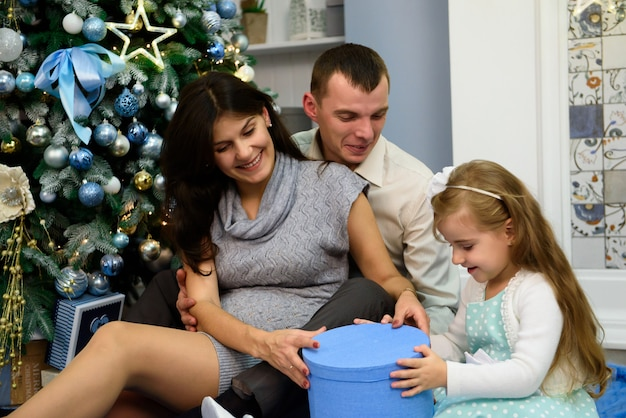 Famiglia felice con regali di natale in salotto.